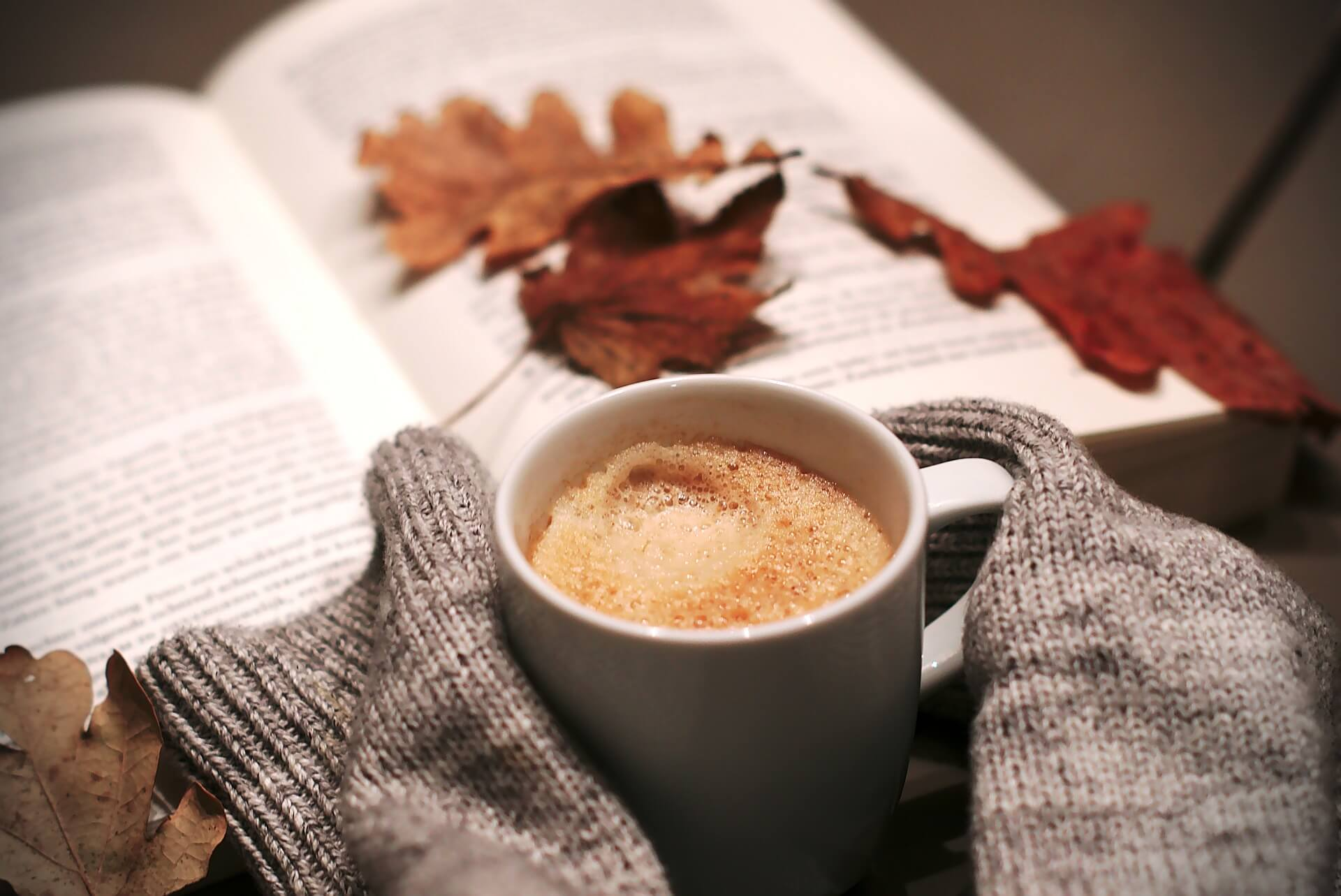 Hands covered by long sleeves and holding a mug of coffee. A book in the background with Autumn leaves on it