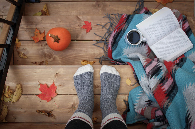 feet with socks on, a small pumpkin and autumn leaves