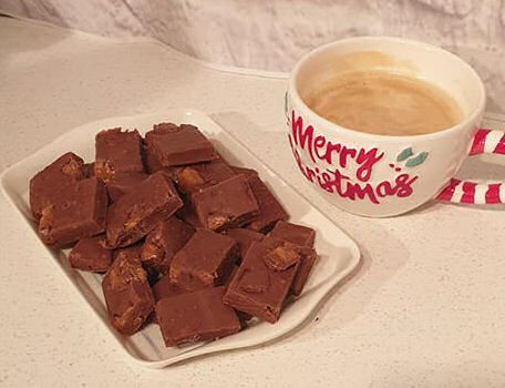 Mars bar fudge with a cup of coffee in a mug that says Merry Christmas on the front